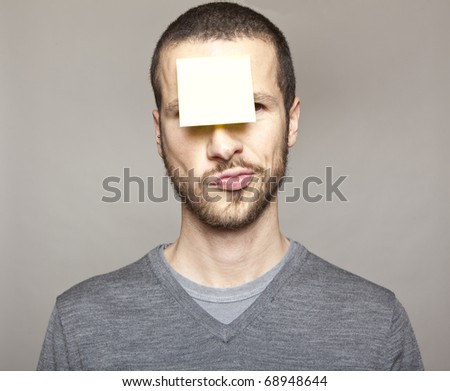 young man with blank note on the face - stock photo