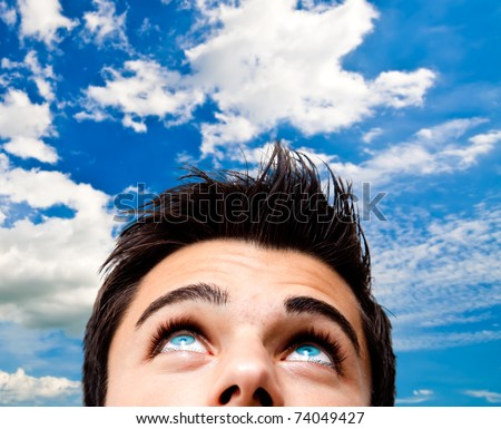 Young man with blue eyes looking high at the sky - stock photo