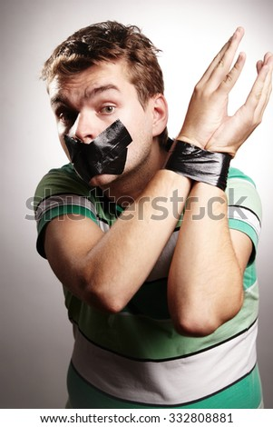 Young man with bonded mouth and hands by black tape - stock photo