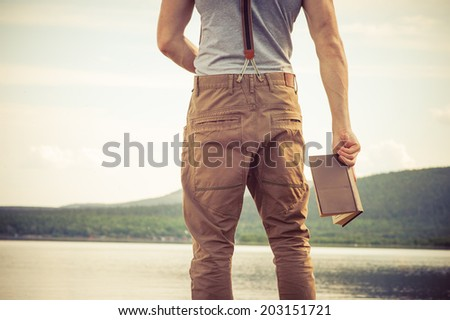 Young Man with book outdoor lake on background Summer vacations and Lifestyle concept - stock photo