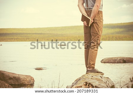 Young Man with book standing outdoor with lake on background Summer vacations and Lifestyle concept retro colors - stock photo