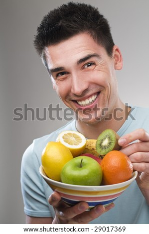 young man with bowl of  fruit close up shoot - stock photo