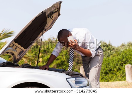 young man with broken down car with bonnet open calling for help - stock photo