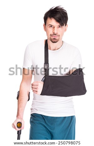 Young man with broken leg and hand is using crutch isolated on white background. - stock photo
