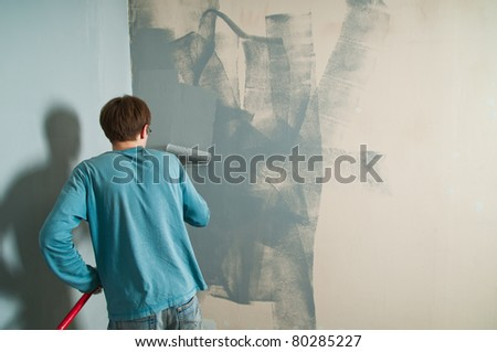 Young man with brush painting the wall - stock photo