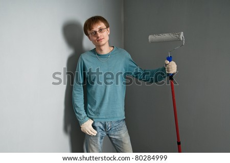 Young man with brush posing against just painted wall - stock photo