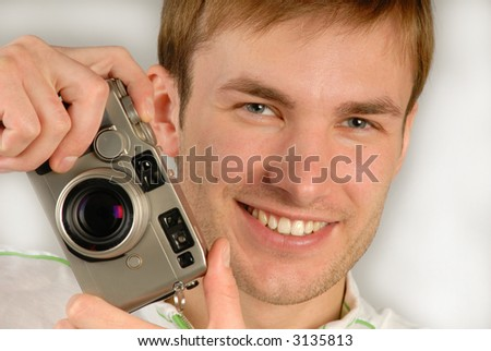 young man with  camera in  hand specifies  finger, close up - stock photo