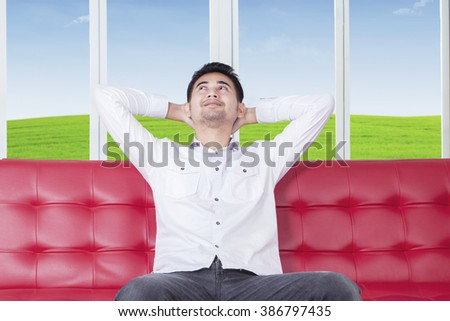 Young man with casual clothes sitting on sofa and looks happy, looking up while smiling - stock photo
