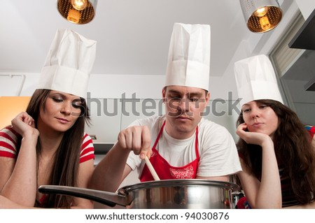 Young man with chef's hat stirring food while two girls are watching