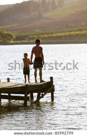 Young man with child at sunset - stock photo