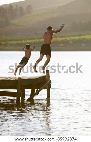 Young man with child jumping to water - stock photo