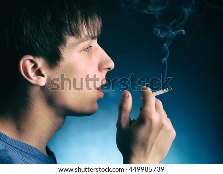 Young Man with Cigarette in the Dark Room - stock photo
