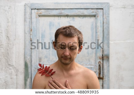 Young man with closed eyes against a shabby door