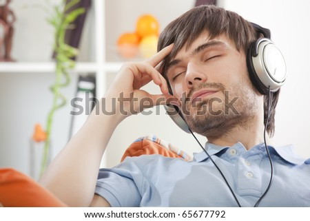 young man with closed eyes and earphones hearing music - stock photo