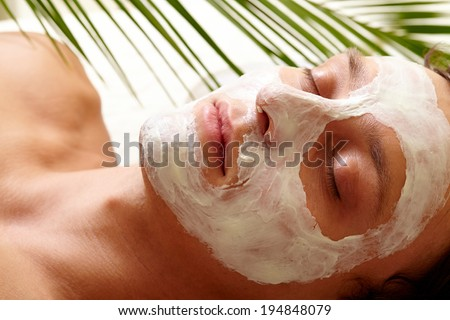 Young man with closed eyes having pore cleaning mask on his face - stock photo