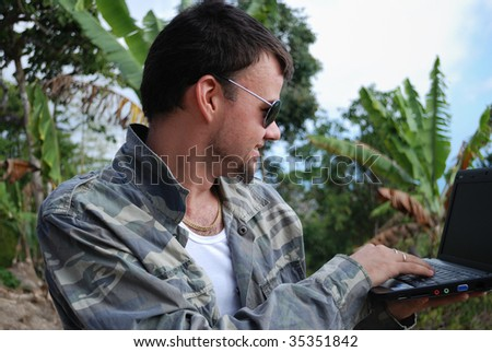 Young man with computer and its new workplace in jungle - stock photo