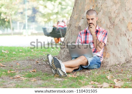 Young Man With Computer at Park - stock photo