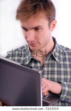 Young  man with concentration works on  computer,  white background - stock photo