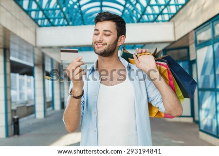 Young man with credit card and shopping bags - stock photo