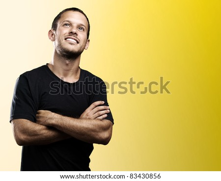 young man with crossed arms on a yellow background - stock photo