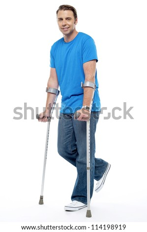 Young man with crutches trying to walk. Accidental case - stock photo