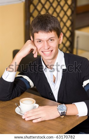 Young man with cup of coffee in cafe