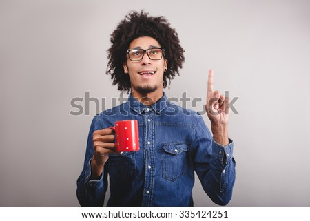 young man with cup of tea  having an idea - stock photo