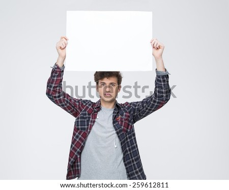 Young man with curly hair holding blank billboard - stock photo