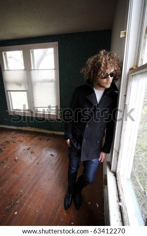 Young man with curly hair looking out the window of an abandoned house.