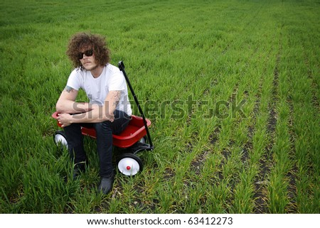 Young man with curly hair sitting in a red wagon in a field.