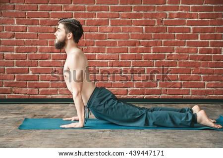 Young man with dark hair and beard wearing trousers doing yoga position on blue matt at wall background, copy space, portrait, cobra pose bhujangasana asana. - stock photo