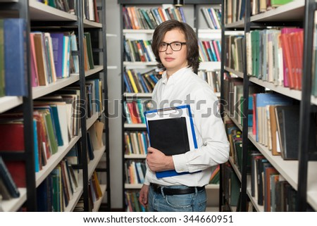 young man with dark hair standing and holding a black copy book and a note pad between book shelves in the library, looking in front of him, slightly turned, a concept of studying