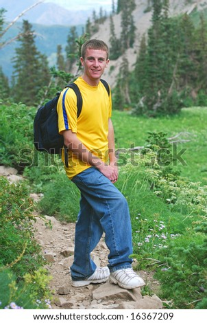 Young man with day backpack hiking in the mountains.