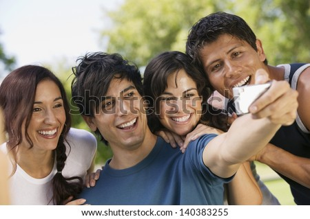Young man with digital camera photographing himself and three friends - stock photo