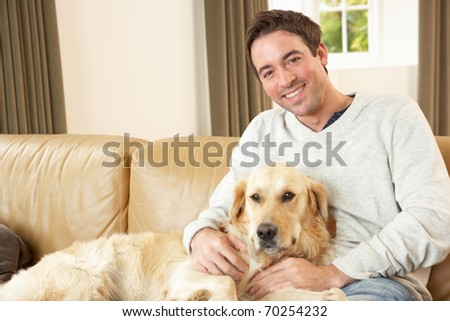 Young man with dog sitting on sofa - stock photo