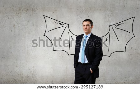 Young man with drawn wings behind back - stock photo