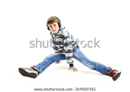 Young man with ear-phones learns to dance hip-hop. Isolated on white background - stock photo