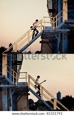 young man with electric guitar going up the stairs and down the metal stairs in industrial zone, at sunset