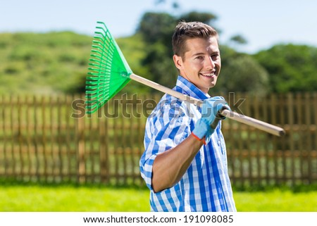 young man with fan rake in his home garden - stock photo