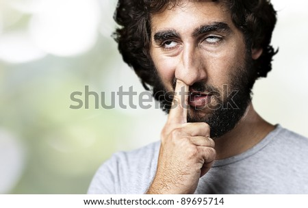 young man with finger in his nose against a nature background - stock photo