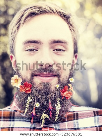 young man with flowers in his beard on natural blurred background close up