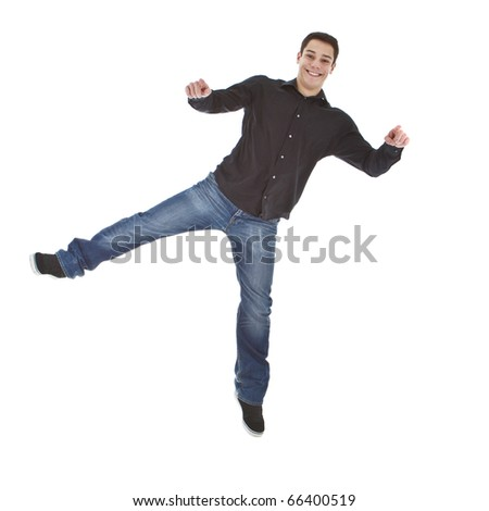 Young man with formal but casual clothes jumoing in joy over white background.