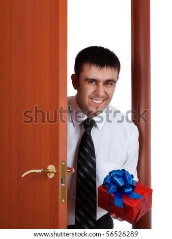 young man with gift opening the door - stock photo