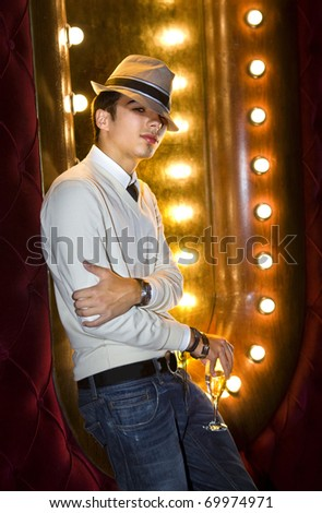 young man with glass of champagne near the mirror in cabaret - stock photo