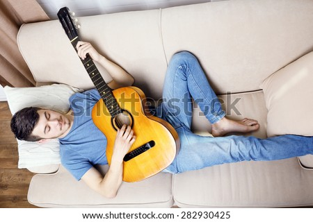 Young man with guitar on sofa in room - stock photo