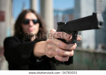 young man with gun in image of the killer in style of the italian film about mafia