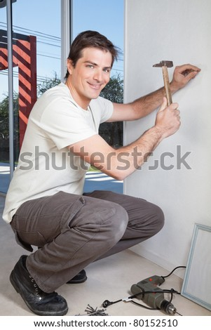 Young man with hammer nailing the wall - stock photo