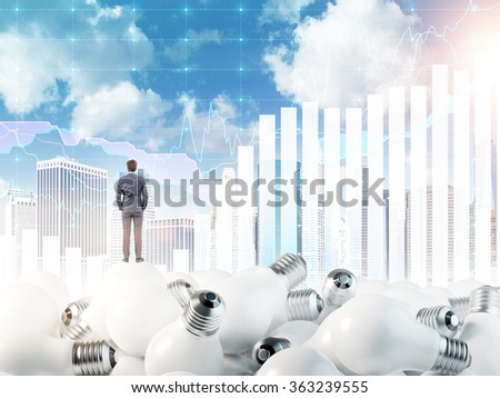 Young man with hands in pockets standing on huge scattered bulbs. Back view. Blue sky and graphs at the background. Concept of new ideas.