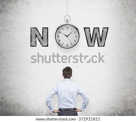 young man with hands on hips thinking about present opportunities and time. A pocket watch and the word 'now' over his head. Concrete background. Back view. Concept of present moment. - stock photo