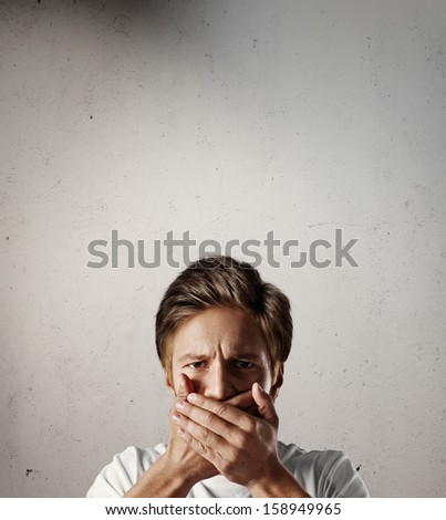 Young man with hands on his mouth - stock photo